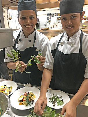 Two young Fijian chefs prepare local fish.